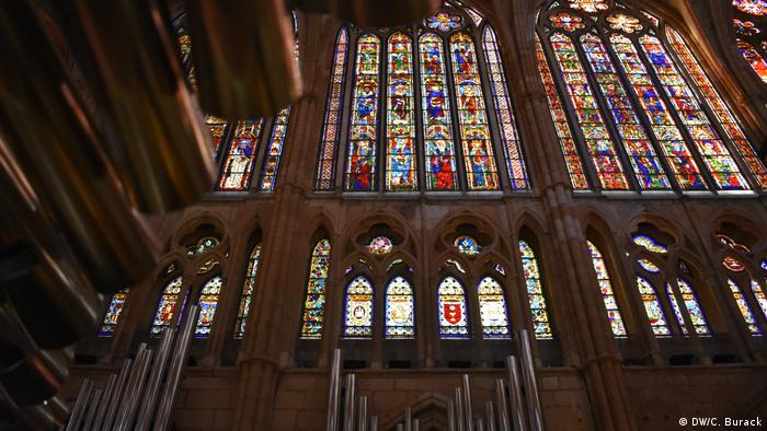 Pipes from Leon's organ catche the reflection of the luminous stained-glass windows