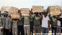 Migrants hold placards during United Nations Secretary-General Antonio Guterres (unseen) visit to Ain Zara detention centre for migrants in the Libyan capital Tripoli