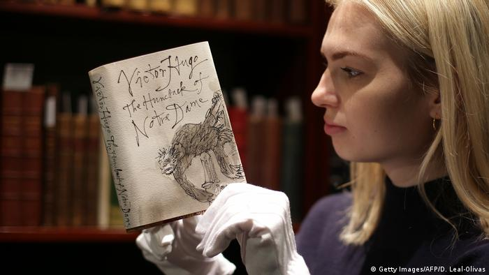 A woman holds the book the Hunchback of Notre Dame (Getty Images/AFP/D. Leal-Olivas)