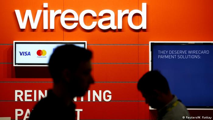 People walk past a Wirecard booth at a games fair in Germany