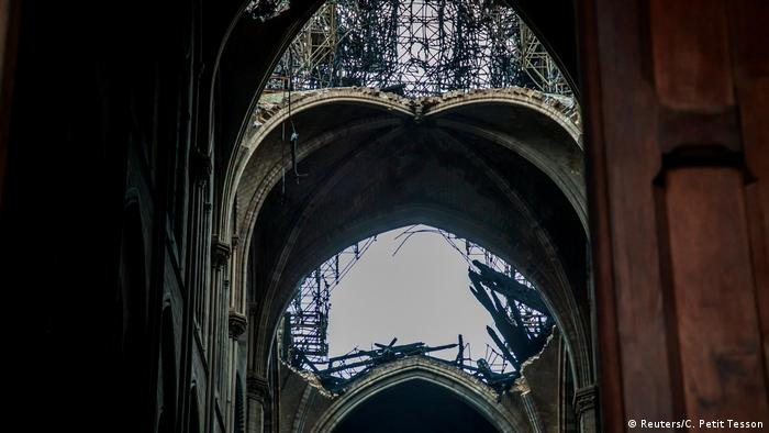 View of sky through church arches partially obscureed by severely damaged latticework of wooden beams (Reuters/C. Petit Tesson)