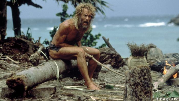 Film Still Cast Away, a man sits on timber on an island (Imago/Prod.DB)