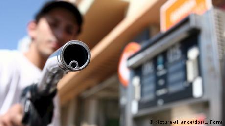 Mann mit Benzinschlauch an einer Tankstelle