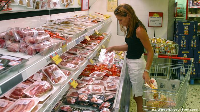 Žena pred hladnjakom sa svježim mesom