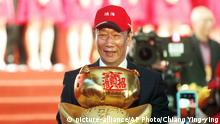 FILE - Terry Gou, chairman of Hon Hai Precision Industry Co. Ltd., also known as Foxconn, holds New Year's lucky charm during the company's annual carnival for employees in Taipei, Taiwan. Gou, head of Foxconn, world's largest electronics supplier, says Wednesday, April 17, 2019, willing to run in Taiwan presidential primary. (AP Photo/Chiang Ying-ying, File) |