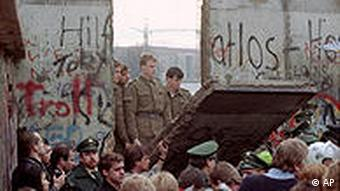 border guards stand behind a section of the berlin wall which crowds on the other side have pulled down