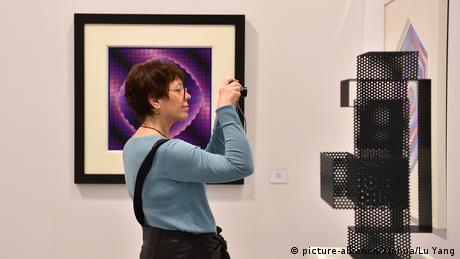 Besucherin fotografiert ein Wandobjekt auf der Art Cologne 2019 (picture-alliance/Xinhua/Lu Yang)