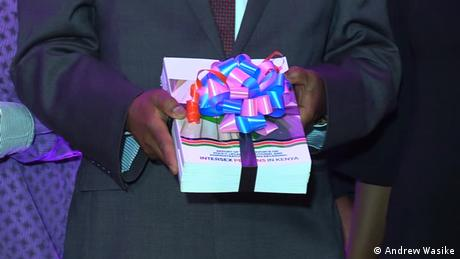 A man in a dark suit holding bound copies of the report by Kenya's taskforce on reforms regarding intersex people wrapped in a gift bow (Andrew Wasike)