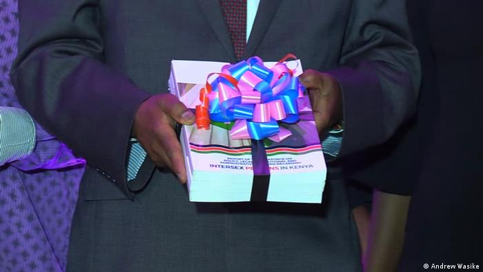 A man in a dark suit holding bound copies of the report by Kenya's taskforce on reforms regarding intersex people wrapped in a gift bow