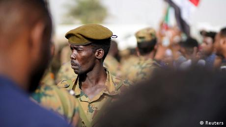 A Sudanese soldier stands guard as demonstrators attend a protest rally demanding Sudanese President Omar Al-Bashir to step down outside the Defence Ministry in Khartoum
