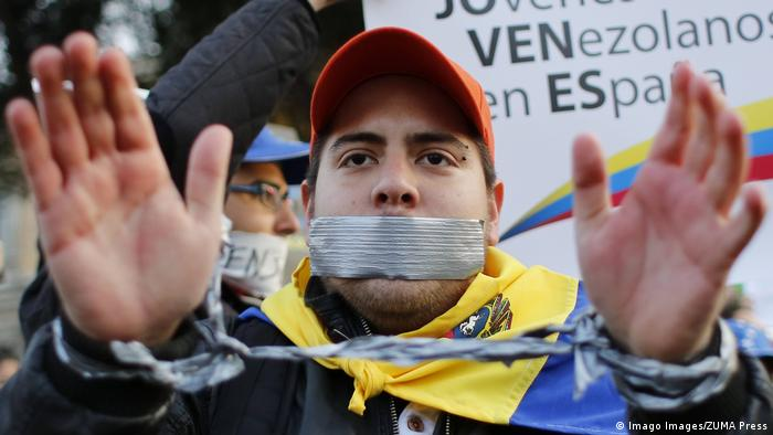 A Venezuelan Student with his mouth sealed and his hands handcuffed as a sign of protest attends a demonstration against the Venezuelan government in Madrid (Imago Images/ZUMA Press)