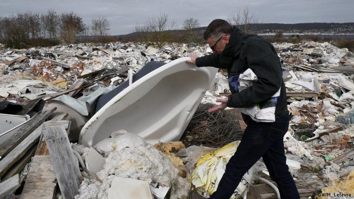 Alban Bernard lifts an old bathtub at an illegal dump near Carrieres-sous-Poissy