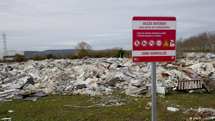 An illegal dump site in Carrieres-sous-Poissy with a red sign warning people away