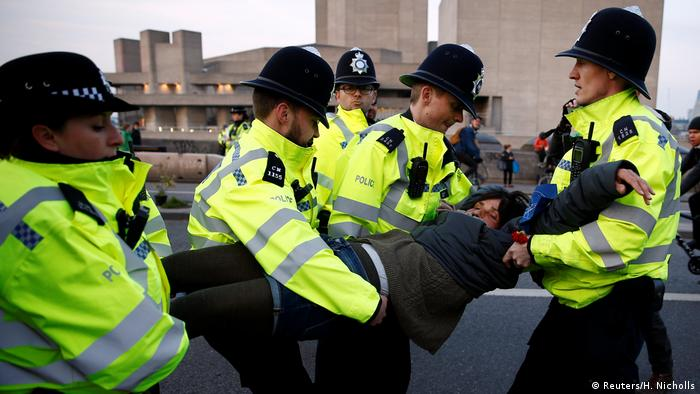Police detain a protester as climate change activists demonstrate during an Extinction Rebellion protest (Reuters/H. Nicholls)