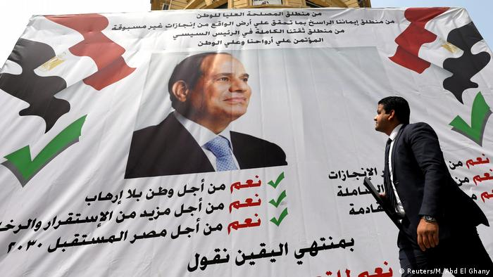 A man looks up at a giant poster of el-Sissi