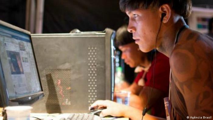 Indígenas estudam informática diante do computador