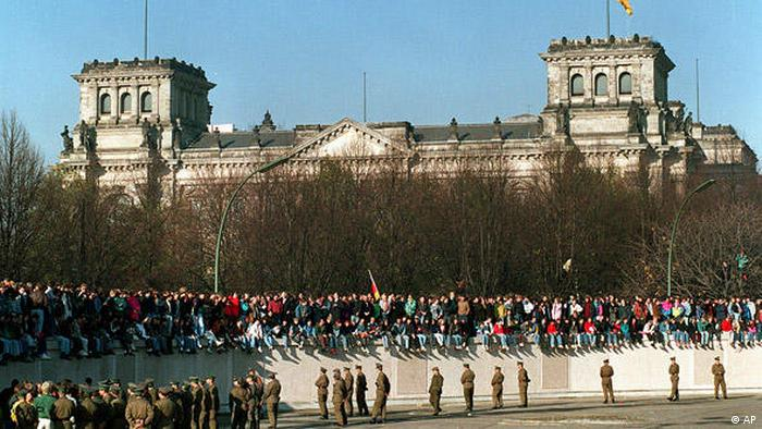 People sit atop the Berlin wall in Berlin with the Reichstag building in the background (AP)