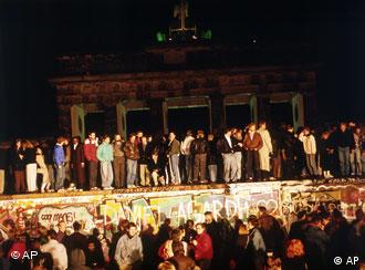 FILE - Berliners from East and West crowd in front of the Brandenburger Tor (Brandenburg Gate), early morning, Nov. 10, 1989, standing atop and below the Berlin Wall, which has divided the city since the end of World War II. The citizens facing the West celebrate the opening of the order that was announced by the East German Communist government hours before. Monday, Nov. 9, 2009 marks the 20th anniversary of the fall of the Berlin Wall. (AP Photo/Jockel Finck)
