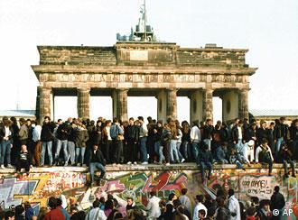 Berlin wall on Nov 10, 1989, with people climbing over it