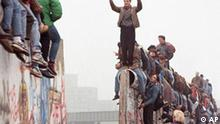 FILE - Berliners celebrate on top of the wall as East Germans (backs to camera) flood through the dismantled Berlin Wall into West Berlin at Potsdamer Platz, in this Nov. 12, 1989 file picture. Monday, Nov. 9, 2009 marks the 20th anniversary of the fall of the Berlin Wall. (AP Photo/Lionel Cironneau)