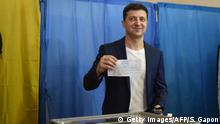Ukrainian comedian and presidential candidate Volodymyr Zelensky shows his ballot to the media at a polling station during the second round of Ukraine's presidential election in Kiev