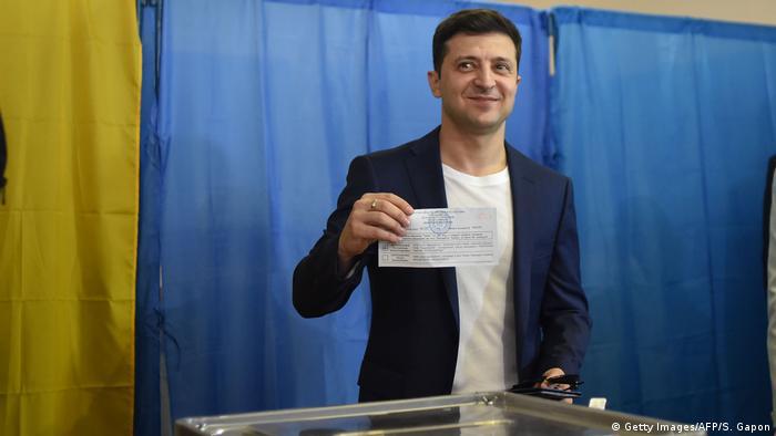 Владимир Зеленский на избирательном участке демонстрирует свой бюллетень для голосования
