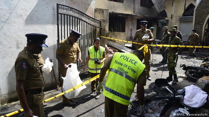 Sri Lankan security personnel and police investigators look through debris outside Zion Church following an explosion in Batticaloa