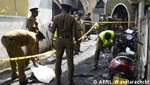 Sri Lankan security personnel and investigators look through debris outside Zion Church. (AFP/L. Wanniarachchi)