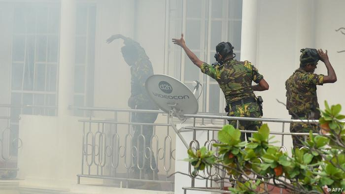 Sri Lankan Special Task Force members outside a house in Colombo amid smoke from a blast