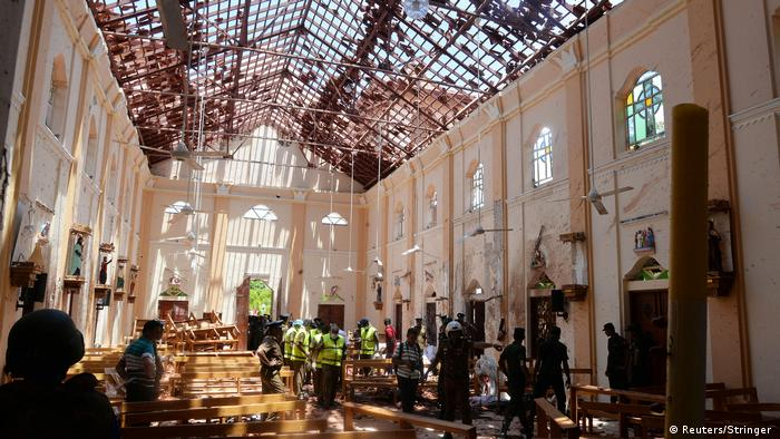 Crime scene officers inspect the site of a bomb blast inside a church in Negombo, Sri Lanka