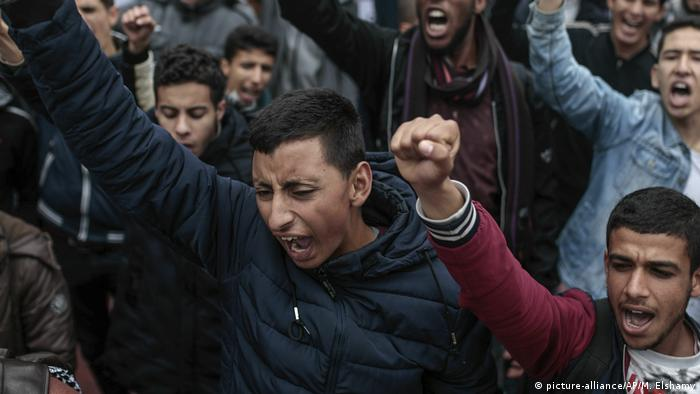 Protesters in Morocco raise their fists as they march through Rabat