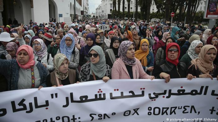 Protesters in Morocco hold a banner as they march through Rabat