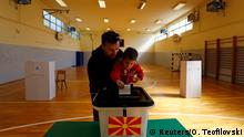 A man and a child cast a ballot for the presidential elections at a polling station in Skopje, North Macedonia April 21, 2019. REUTERS/Ognen Teofilovski