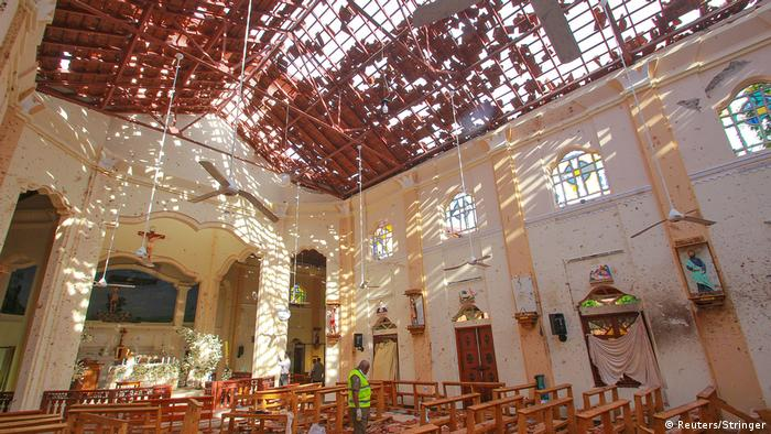 A crime scene official inspects the site of a bomb blast inside a church in Negombo