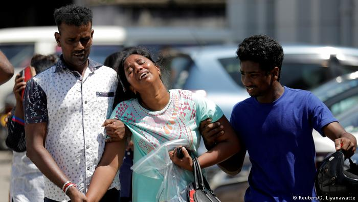 Relatives of victims react at a police mortuary following bomb blasts in Colombo