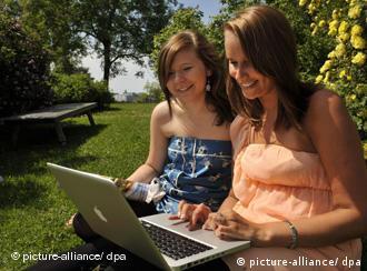 Zwei junge Frauen sitzen mit einem Laptop im Park