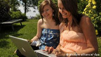 two girls sitting with a laptop in a garden