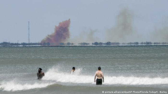 Orange smoke rises over Cape Canaveral