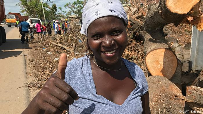 A volunteer in Beira smiles and gives a thumbs up to the camera
