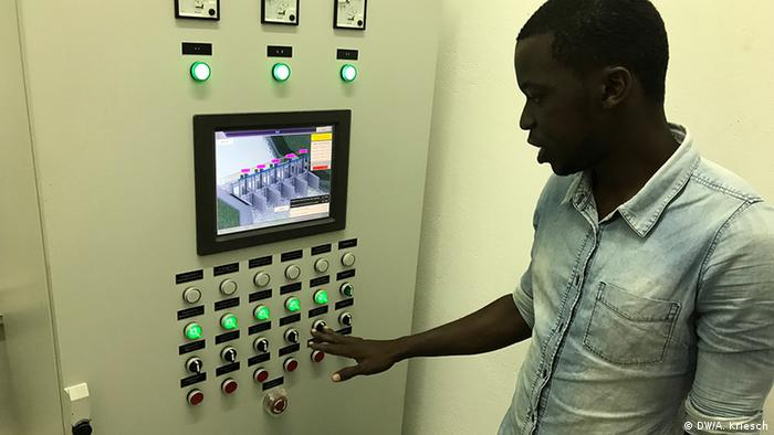 A man inspects a control panel which controls the lock in Beira