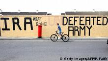A pedestrian walks past graffiti that has been amended to read IRA are done. Defeated Army (Getty Images/AFP/P. Faith)