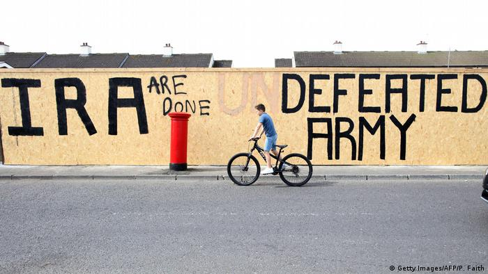 A young cyclist rides past graffiti amened to read IRA are done. Defeated Army instead of IRA undefeated Army. (Getty Images/AFP/P. Faith)