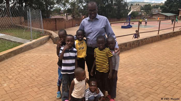 Damas Gisimba poses for the camera with seven young boys inside the Gisimba Memorial Center. More children are playing on a basketball court in the background