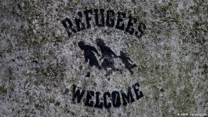 A stencil reading refugees welcome on a wall