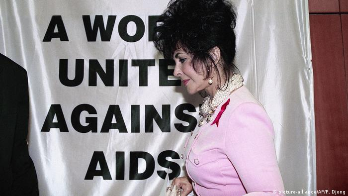 Elizabeth Taylor in front of a t-shirt reading A World United Against AIDS (picture-alliance/AP/P. Djong)