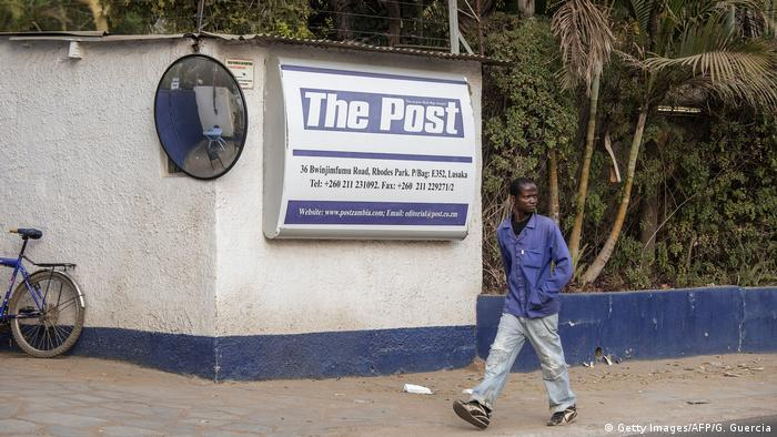 A man in Lusaka walks past the now-closed headquarters of The Post