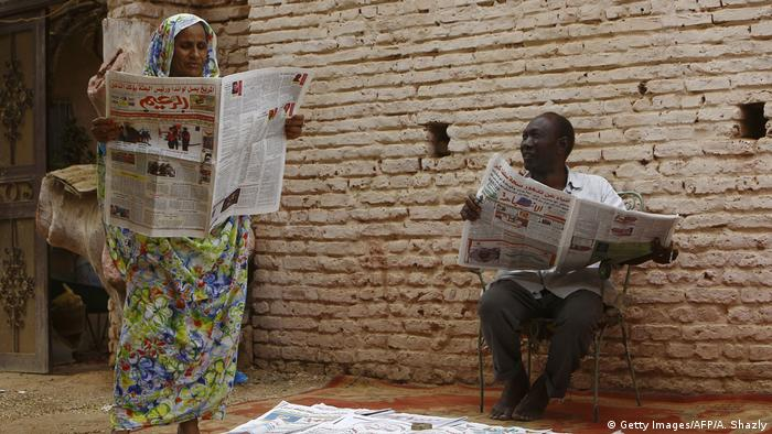 A man and a woman in Sudan read local newspapers on the street (photo: ASHRAF SHAZLY/AFP/Getty Images)