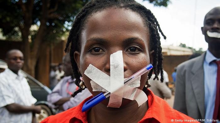 A female protestor in Uganda looks at the camera with a pen taped on her lips (photo: MICHELE SIBILONI/AFP/Getty Images)