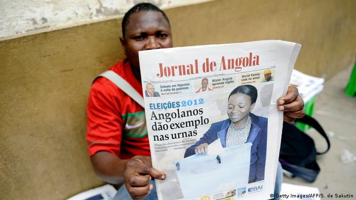 A man in Angola holds up a newspaper to the camera