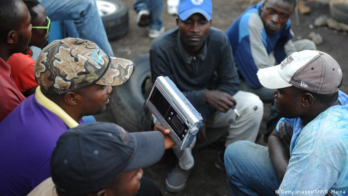 A group of men in DRC gather around a hand-held radio to listen to a broadcast